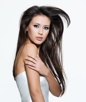 美しい長い茶色の髪を持つ官能的な若い女性、白で隔離ポーズ