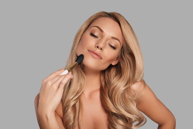 美容製品を適用し、灰色の背景に立って笑っている新鮮な輝く肌を持つ官能的な若い女性