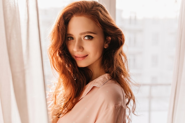 窓の近くに立っている生姜髪の官能的な若い女性。魅力的な白人の女の子の屋内の肖像画。