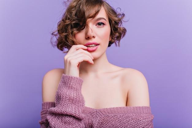 柔らかいウールのセーターでポーズをとる光沢のある短い髪の官能的な若い女性。紫色の壁に孤立した遊び心のある白人の女の子。