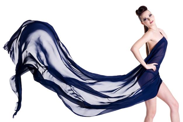白で隔離の青いシフォンでポーズをとって官能的でエレガントな美しい女性