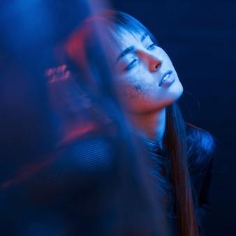 Чувственность и удовольствие. студия снята в темной студии с неоновым светом. портрет молодой девушки