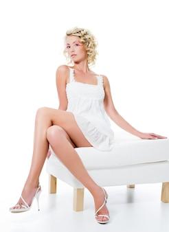 Чувственность привлекательная женщина с красивыми ногами сидит на белом стуле