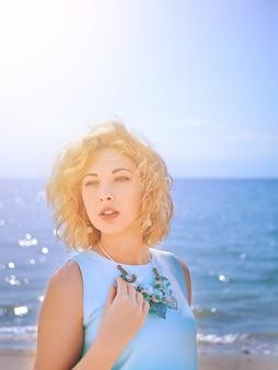 Sensuality blondy woman in cyan dress on the beach