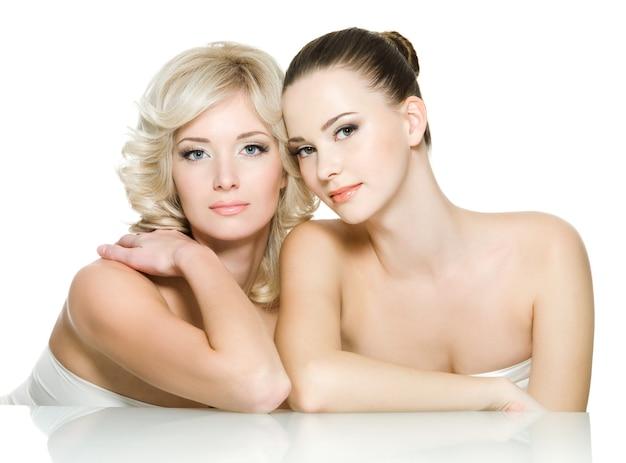 두 명의 아름다운 젊은 성인 여성의 관능 얼굴이 함께 있습니다. 흰색 바탕에 포즈를 취하는 여자