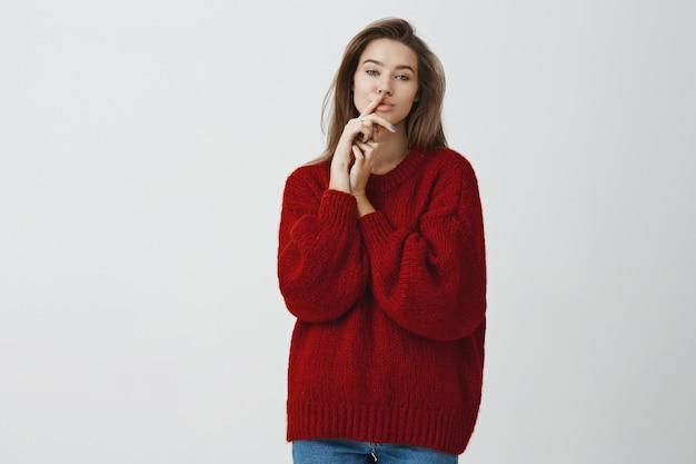 Sensualità, concetto femminile e di bellezza. ritratto di giovane donna sexy flirty e impertinente in maglione invernale sciolto rosso che tiene il dito indice sulle labbra che nasconde segreto impertinente, zittendo sul muro bianco