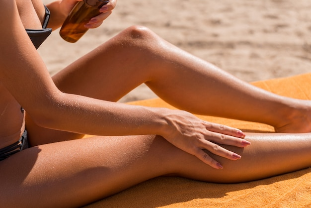 Sensuous slim woman applying suntan oil