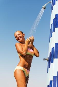 Sensuous slim woman taking shower at the beach