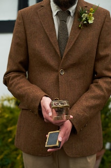 Sentence. hands of a man in a brown jacket holding a glass gift box with a ring.