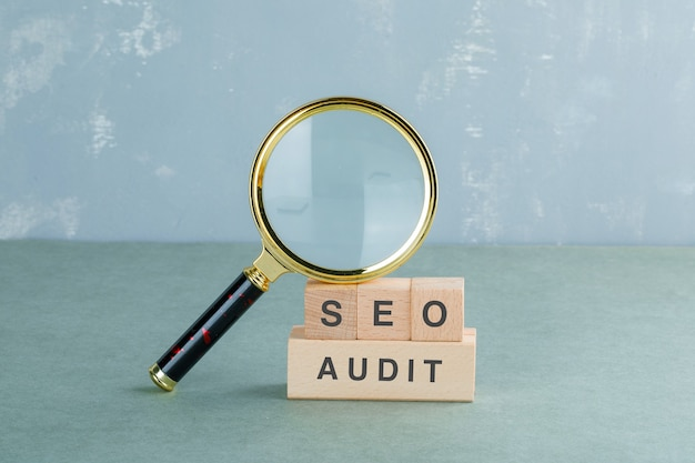 Seo analysis and business concept with wooden blocks with words on it, magnifying glass side view.
