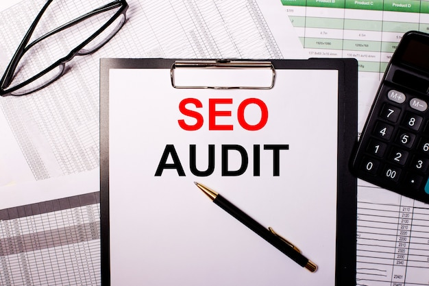 Seo audit написано на белом листе бумаги рядом с очками и калькулятором.
