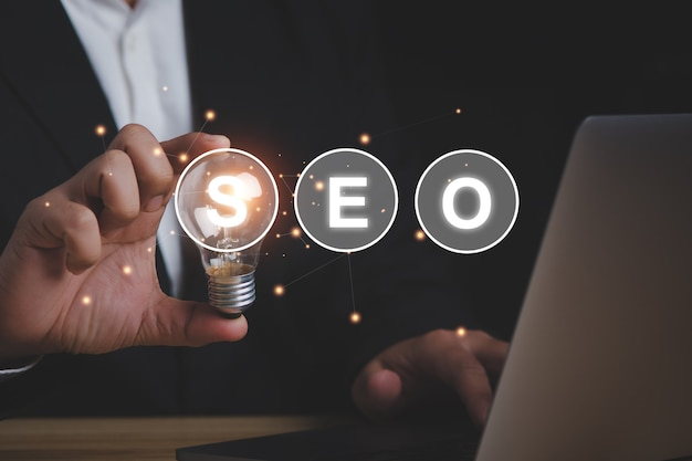 Seo検索エンジン最適化の概念のビジネスマンは、アイデアが機能するために電球を持っています。