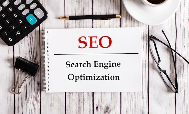 Seo поисковая оптимизация написана в белом блокноте рядом с калькулятором, кофе, очками и ручкой. бизнес-концепция