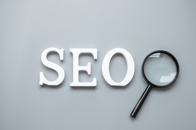 Seo (search engine optimization) text and magnifying glass on gray . idea, vision, strategy, analysis, keyword and content concept