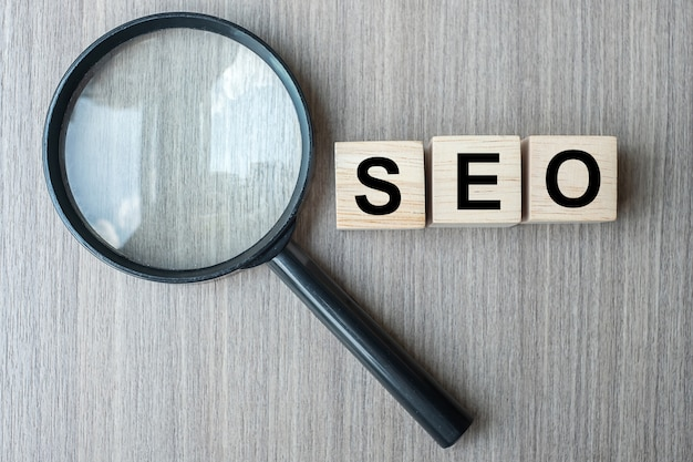 Seo (search engine optimization) text wooden cubes and magnifying