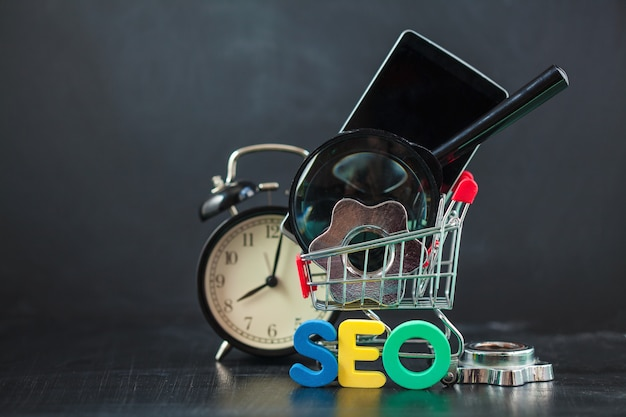 Seo поисковая оптимизация цветные буквы seo с часами, увеличительным, смартфоном, шестеренками в корзине.