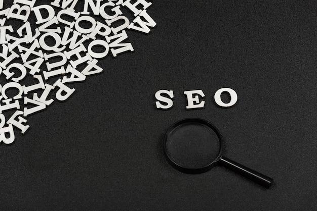 木製の文字と黒い背景に虫眼鏡から書かれたseoの単語。検索エンジン最適化