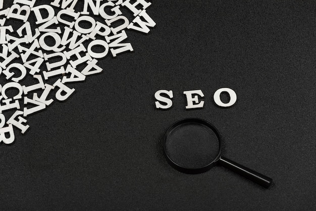 Seo word written from wood letters and magnifying glass on black background. search engine optimization