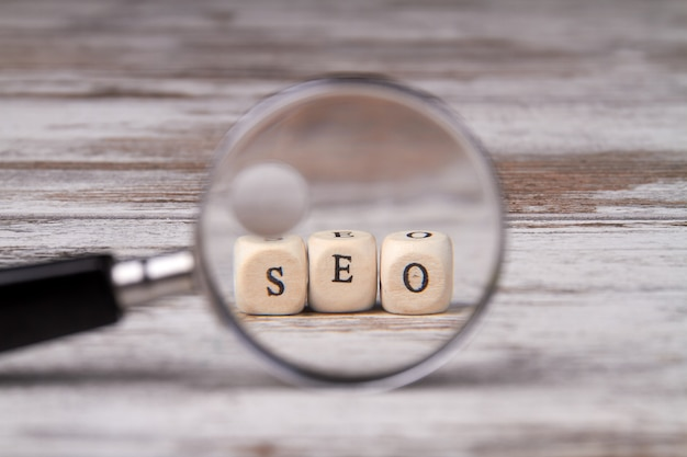 Seo written on wood block and magnifier on wooden background.