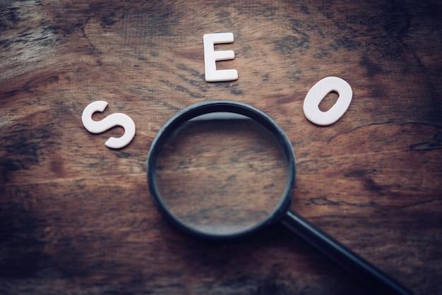 Слова «seo» и увеличительное стекло на деревянном полу - концепция поисковой оптимизации