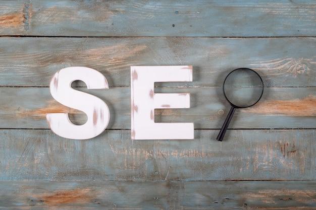 白い文字と虫眼鏡で形成されたseoの単語。検索エンジン最適化の概念。