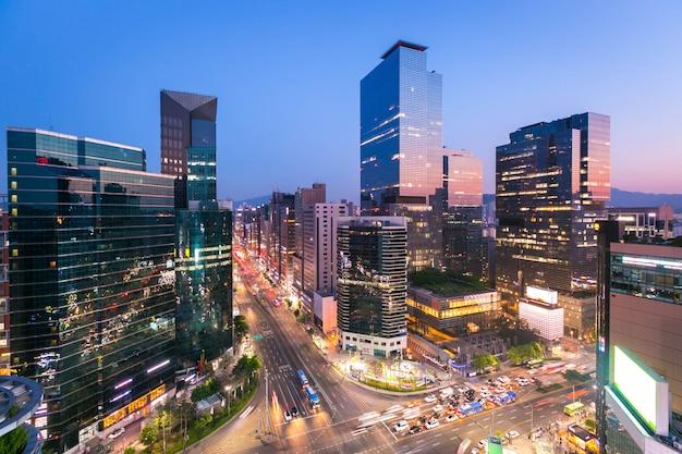 韓国ソウル江南の夜の交差点でソウル市スカイリングと高層ビルと交通。