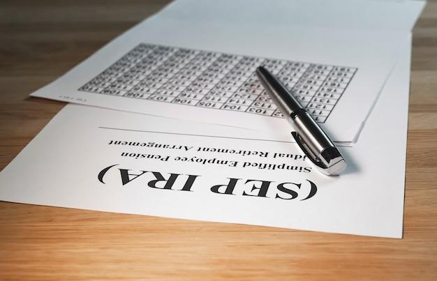 펜과 계산이 있는 나무 테이블에 있는 sep ira 종이 문서