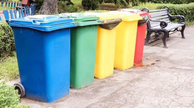 Отдельные контейнеры для вывоза мусора в парке. разноцветные уличные мусорные баки на улице. контейнеры выборочный сбор мусора. концепция загрязнения окружающей среды.