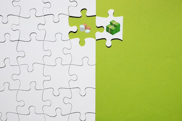 Separation of coin and bank note on puzzle on green background