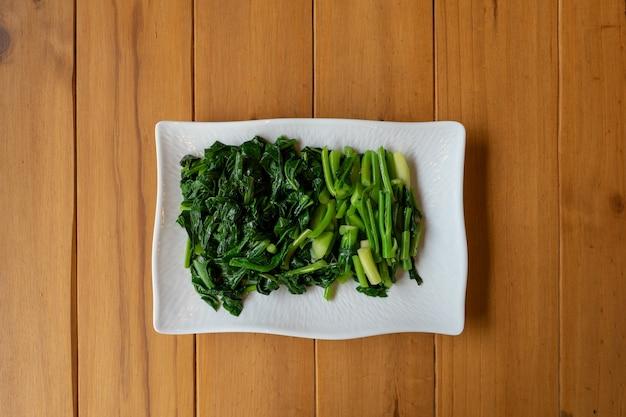 木のテーブルの白い長方形の上に、スライドさせて茹でた中国(タイ)のケール野菜を分けます。