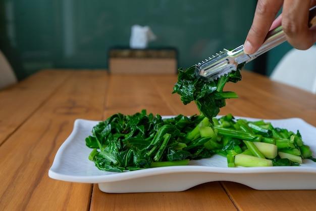 木のテーブルの白い長方形の上に、スライドさせて茹でた中国(タイ)のケール野菜を分けます。 Premium写真