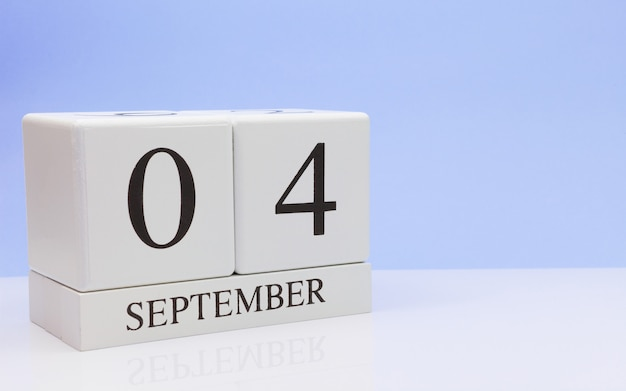 September 04st. day 4 of month, daily calendar on white table with reflection