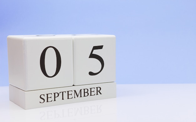 September 05st. day 5 of month, daily calendar on white table with reflection