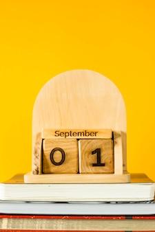 1 сентября на деревянном календаре среди учебников учиться на желтом фоне