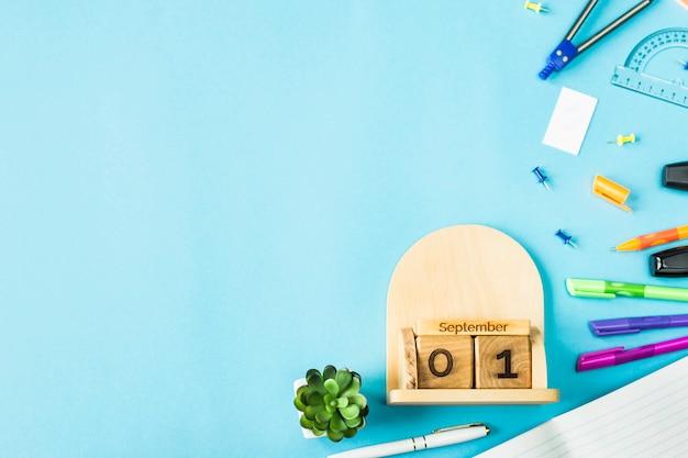 1 сентября на деревянном календаре среди припасов для учебы на синем фоне