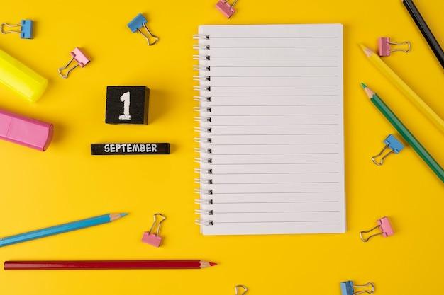 1 сентября на деревянном календаре среди принадлежностей для учебы на желтом фоне снова в школу