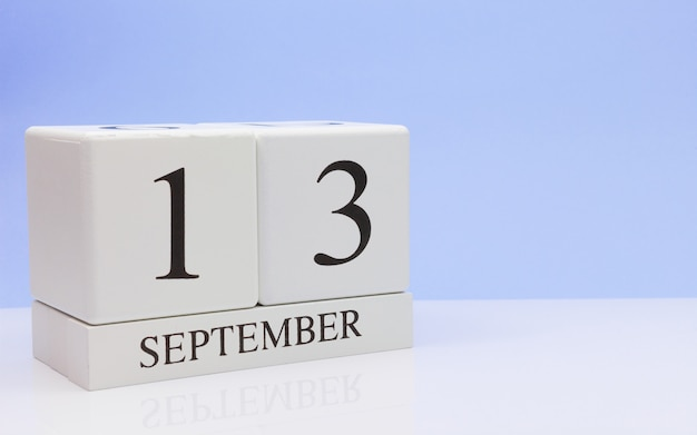 September 13st. day 13 of month, daily calendar on white table with reflection
