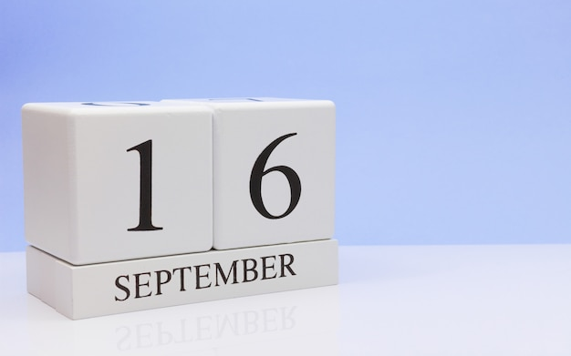 September 16st. day 16 of month, daily calendar on white table with reflection