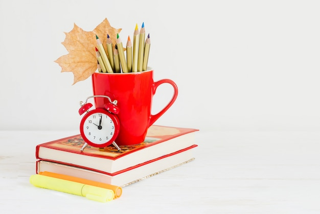 September 1st concept. red alarm clock, cup, color pencils, books and maple leaf. back to school concept