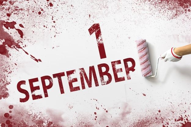 9月1日。月の1日目、カレンダーの日付。手は赤いペンキでローラーを保持し、白い背景にカレンダーの日付を書き込みます。秋の月、年の日の概念。