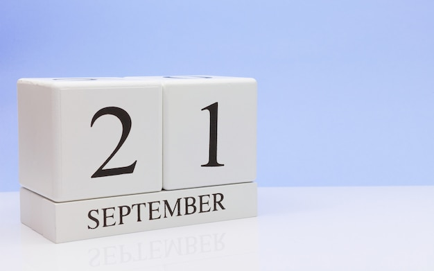 September 21st. day 21 of month, daily calendar on white table with reflection