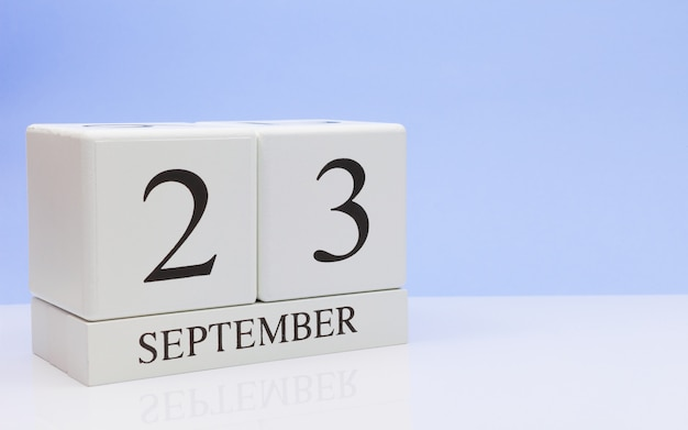 September 23st. day 23 of month, daily calendar on white table with reflection
