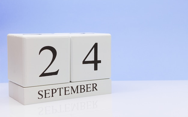 September 24st. day 24 of month, daily calendar on white table with reflection