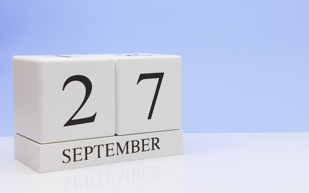 September 27st. day 27 of month, daily calendar on white table with reflection