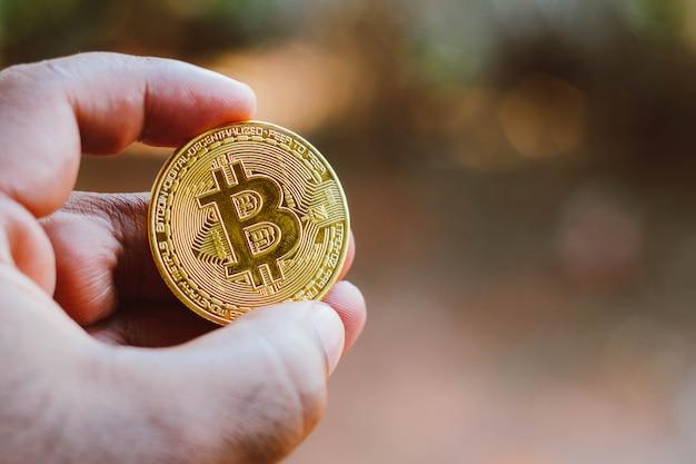 8 сентября 2021 года, бразилия. на этой фотографии изображен мужчина, показывающий золотую монету биткойн.