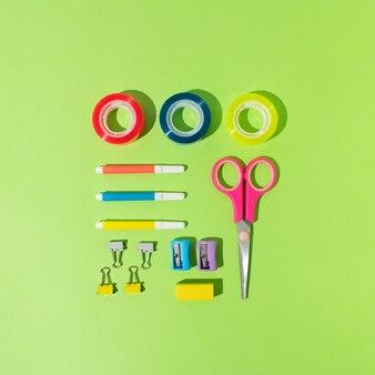 Сентябрь, снова в школу, концепция офиса. различные школьные / офисные принадлежности. карандаши для квадратной компоновки, ленты, ластики, булавки, линейки, маркеры, скрепки. ярко-зеленый фон.