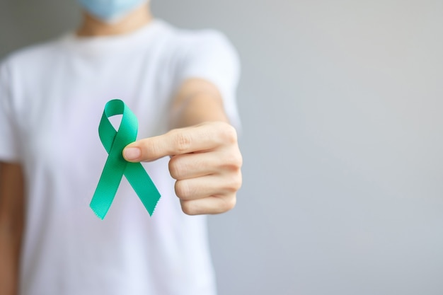 September ovarian cancer awareness month, woman holding teal ribbon color for supporting people living, and illness. healthcare and world cancer day concepts