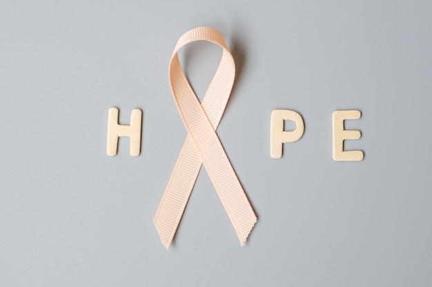 9월 자궁암 인식의 달, 생존자와 질병을 지원하는 피치 리본. 의료 및 세계 암의 날 개념