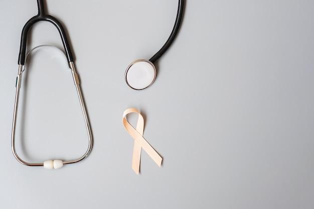 9월 자궁암 인식의 달, 청진기가 달린 복숭아 리본은 생활과 질병을 지원하는 사람들을 지원합니다. 의료 및 세계 암의 날 개념