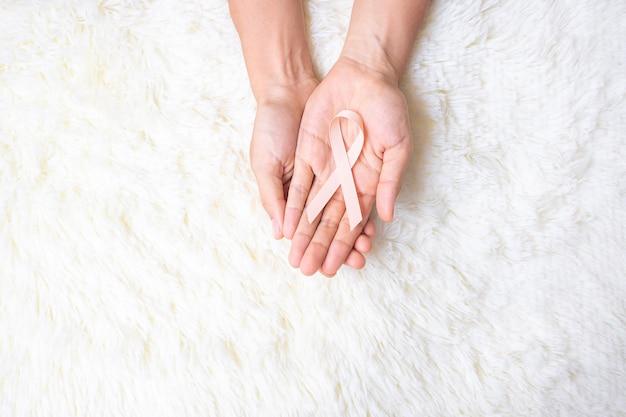 9월 자궁암 인식의 달, 여성의 손이 살아있는 사람들과 질병을 지원하기 위해 피치 리본을 들고 있습니다. 의료 및 세계 암의 날 개념